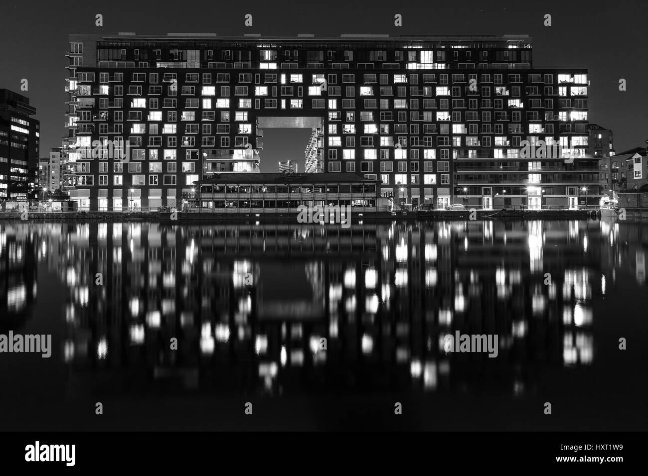 Building at night in marina with reflections of lights, London Docklands - Stock Image