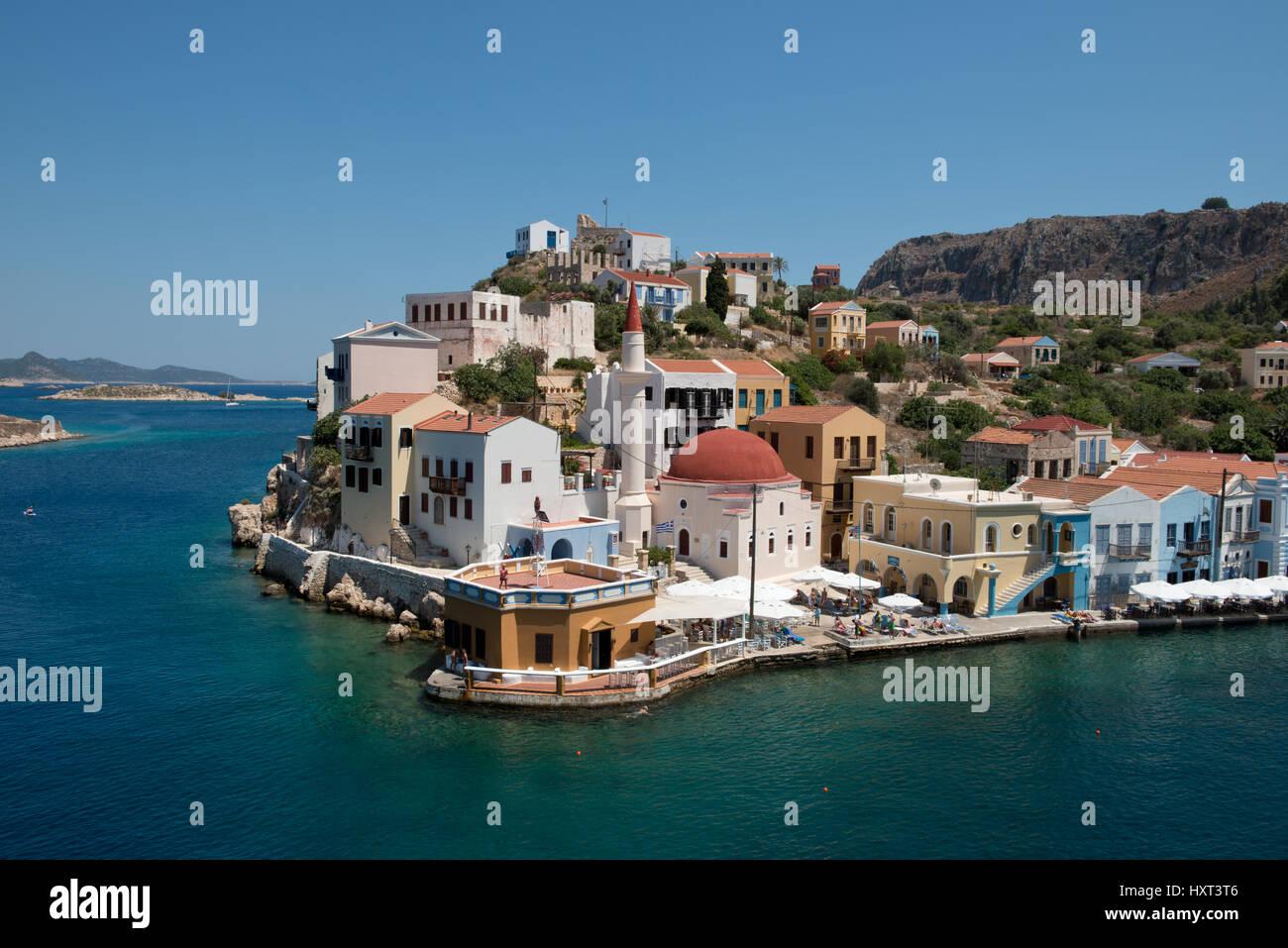 Hafeneinfahrt mit türkisgrünem Wasser, Moschee, bunten Häusern und kahlen Hügeln, Insel Kastellorizo, - Stock Image