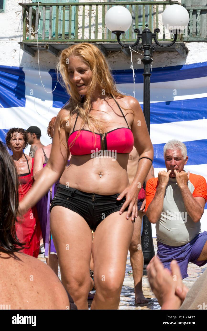 tanzende blonde Frau in Bikini vor griechischer Fahne und Strassenlaterne, Insel Kastellorizo, Dodekanes, Griechenland - Stock Image