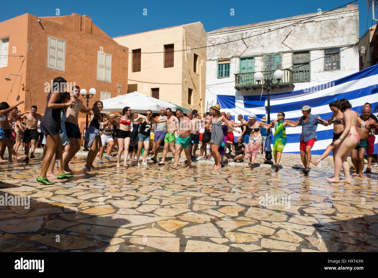 tanzende Menschen in Badekleidung auf Dorfplatz, dahinter farbige Häuser und griechische Fahne, Insel Kastellorizo, - Stock Image
