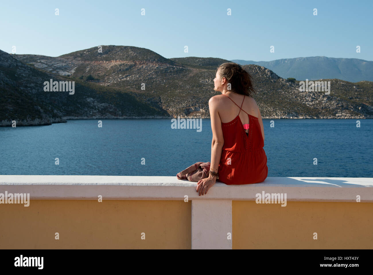Mädchen in rotem Kleid sitzt auf Quaimauer, sieht auf Meer, dahinter kahle Hügel, Insel Kastellorizo, - Stock Image