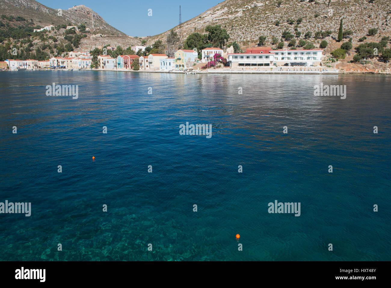 türkisblaues Wasser einer Bucht mit bunten Häusern und kahlem Hügel, Insel Kastellorizo, Dodekanes, - Stock Image