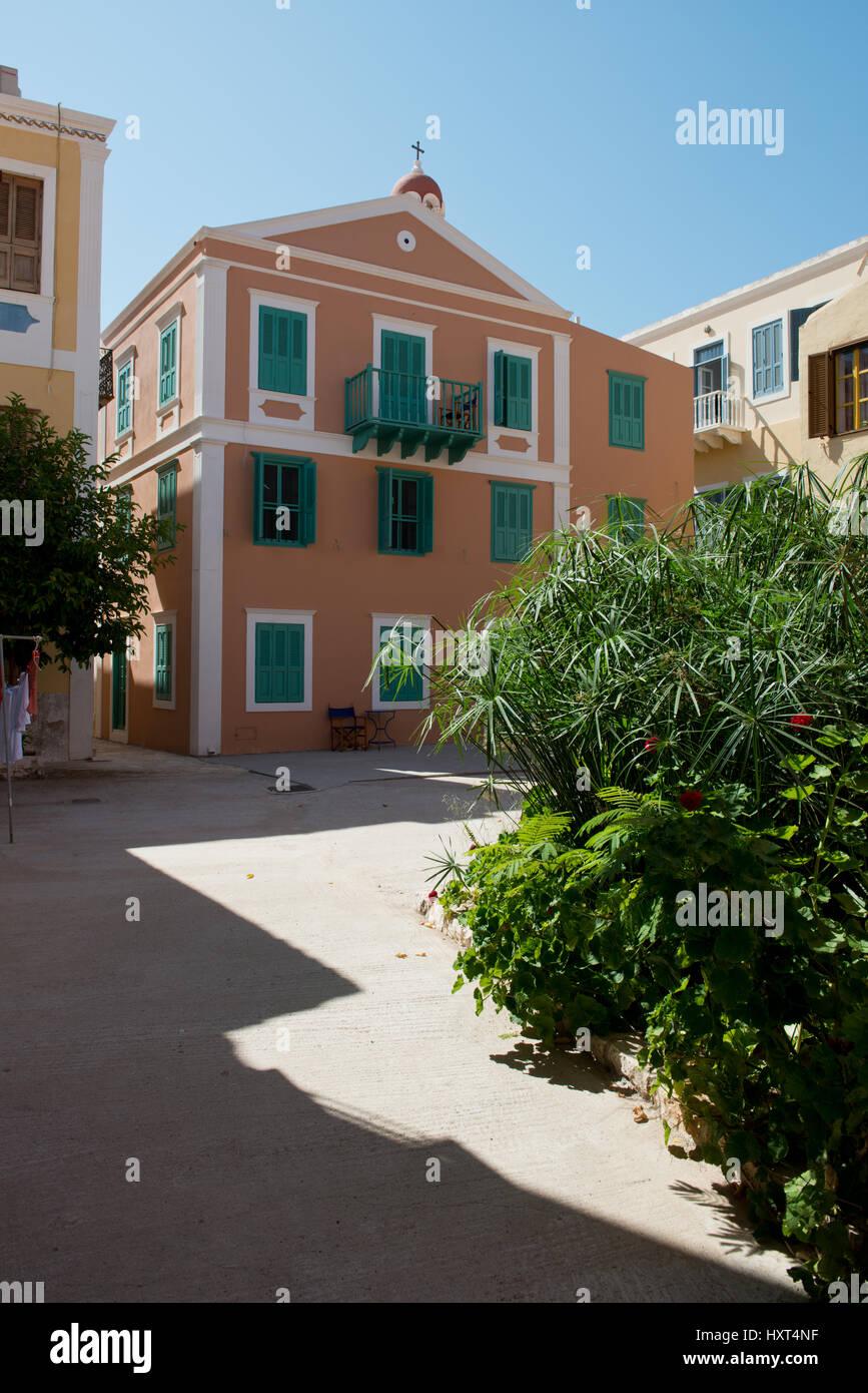 orangefarbenes Haus mit grünen Fensterläden auf Dorfplatz, rechts Grünpflanzen, Insel Kastellorizo, Dodekanes, Griechenland Stock Photo