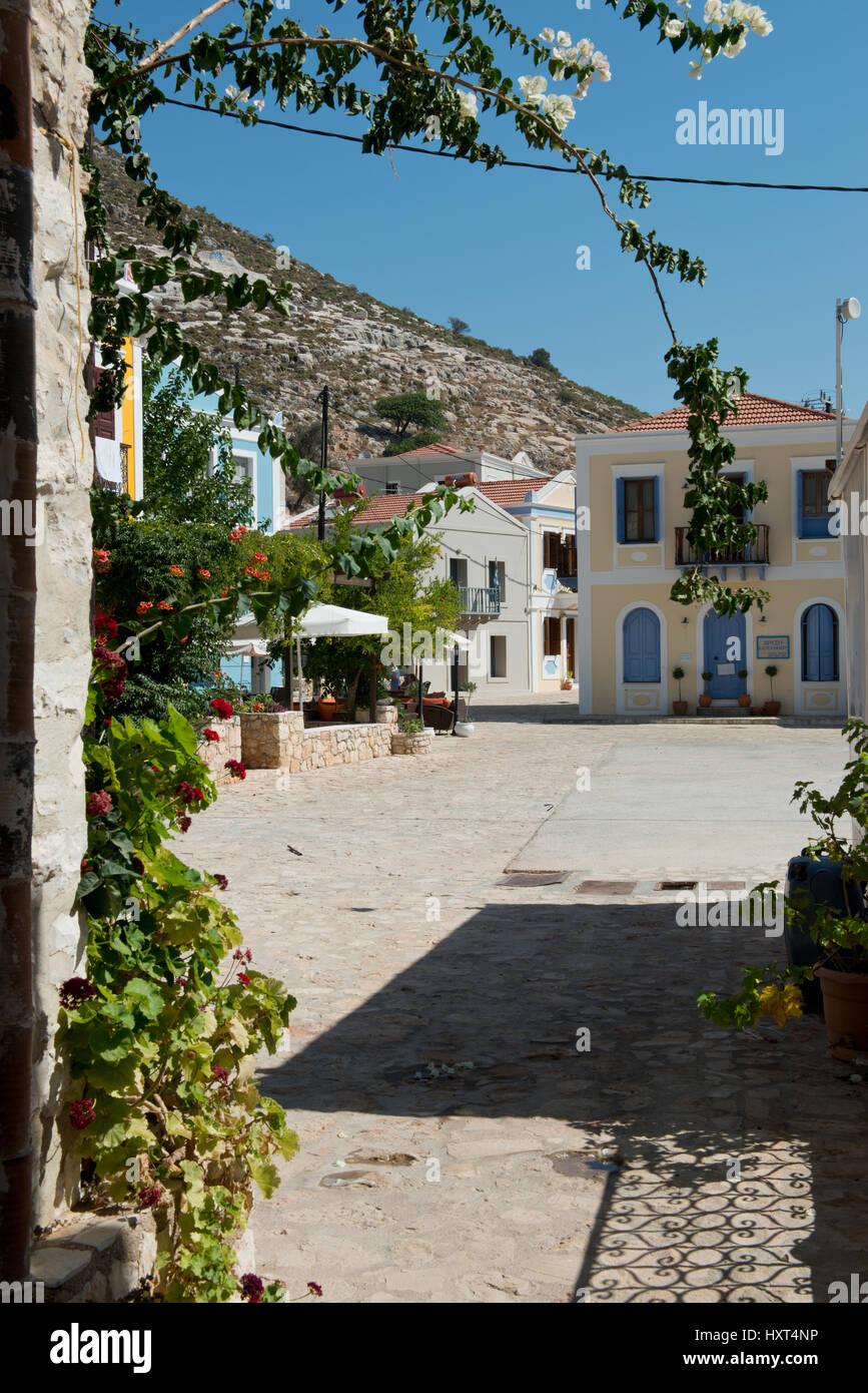 Dorfplatz mit bunten Häusern, Bougainvillea Pflanze, Blumentöpfen und Berg im Hintergrund, Insel Kastellorizo, Dodekanes, Stock Photo