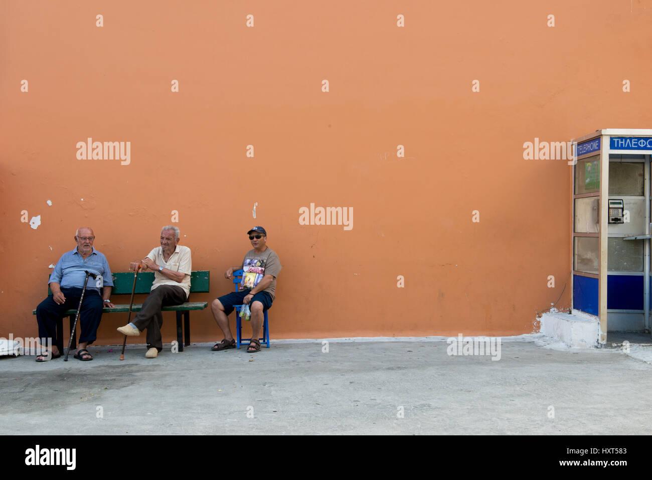 drei ältere Männer sitzen auf einer Bank vor einer lachsfarbenen Hauswand, seitlich eine Telefonzelle, - Stock Image