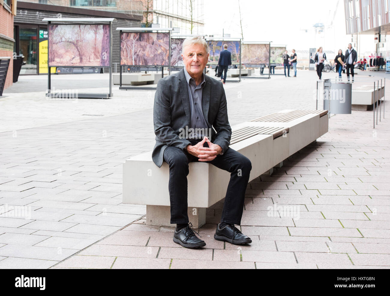 Hamburg, Germany. 30th Mar, 2017. Art Wolfe sits in front of his works on display as part of the city of Hamburg's - Stock Image