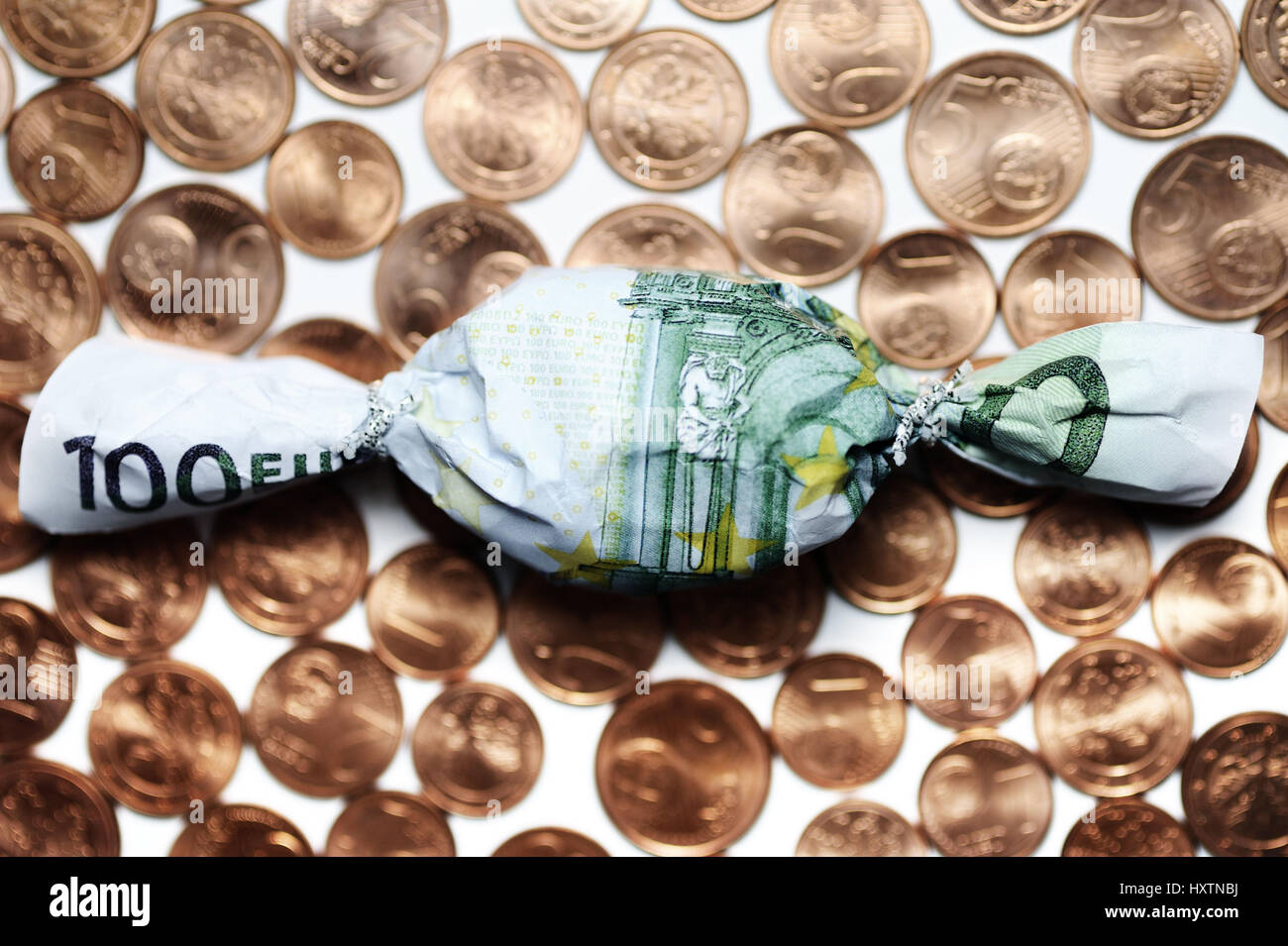 Sweet in euro-light hundred muffledly on cent coins, bonus payments, Bonbon in Hundert-Euro-Schein eingewickelt auf Cent-Münzen, Bonuszahlungen Stock Photo