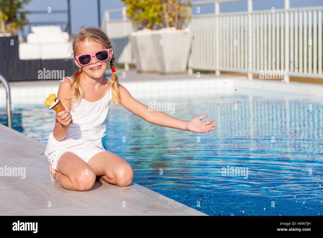 Happy little girl with ice cream sitting near a swimming - Where is my nearest swimming pool ...