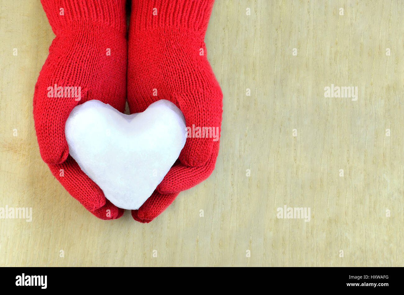 Snow heart in red gloves on wooden surface - Stock Image