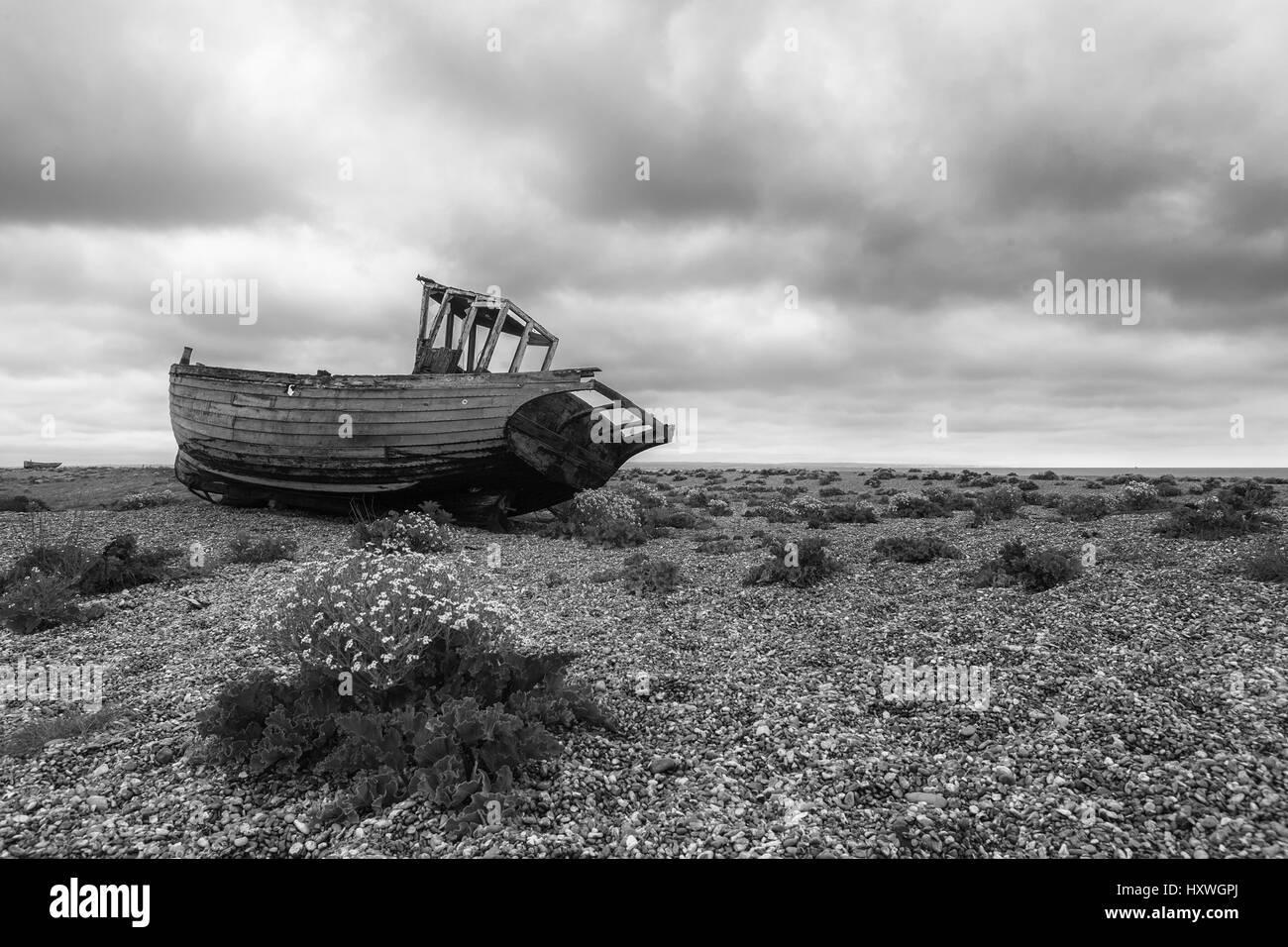 Fishing boat abandoned on the shingle beach at Dungeness, Kent, England, UK - Stock Image