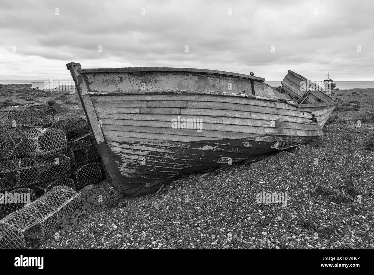 The wreck of an old wooden fishing boat on the shingle beach at Dungeness, Kent, England, UK - Stock Image