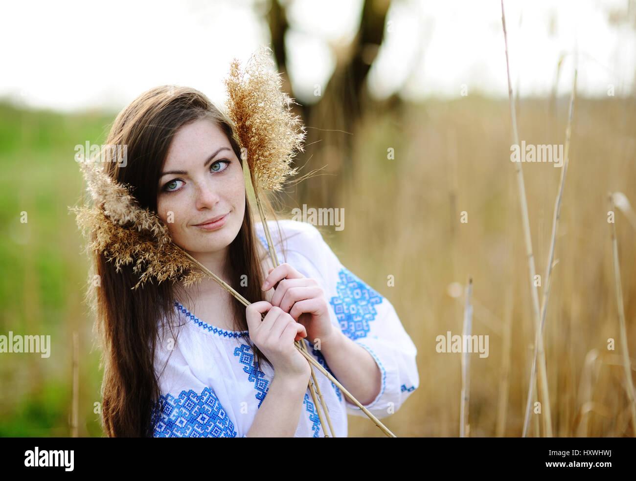 Slavic girl in Ukrainian shirt holding ears of corn - Stock Image