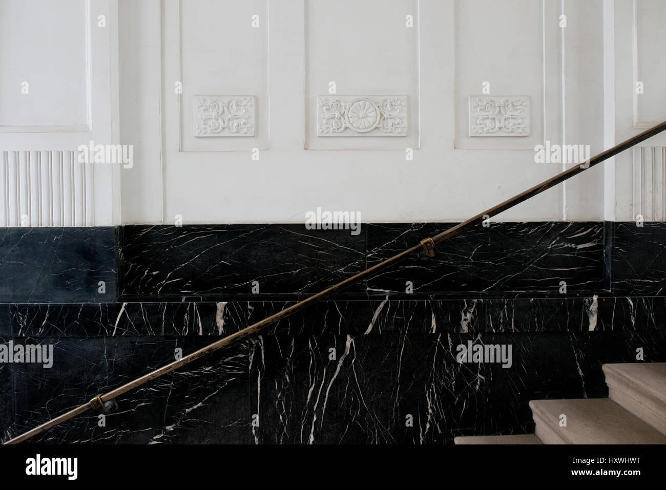 Treppenhaus mit schwarzer Marmorverkleidung, Treppengeländer aus Messing und Stukkaturen in Wien, Österreich - Stock Image