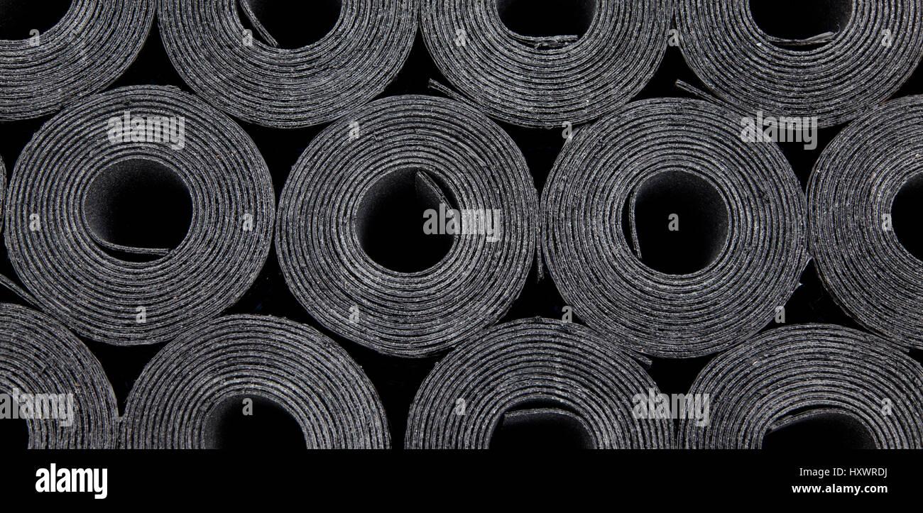 Rolls of new black roof coating or bitumen - Stock Image