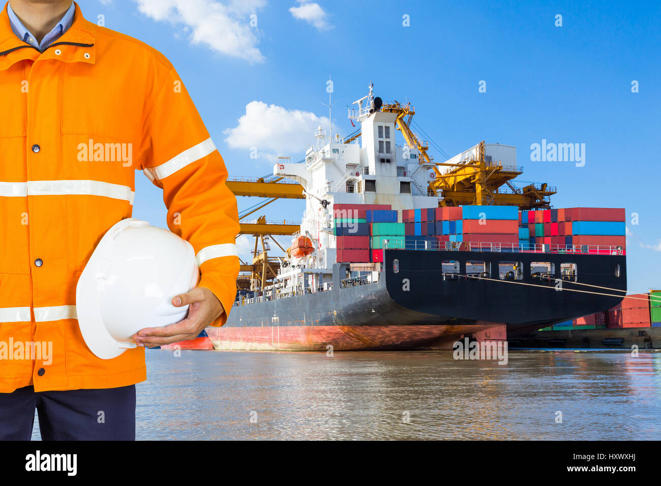 Engineer dockers wearing safety coat and holding a helmet in front of an industrial harbor with cranes and a container - Stock Image