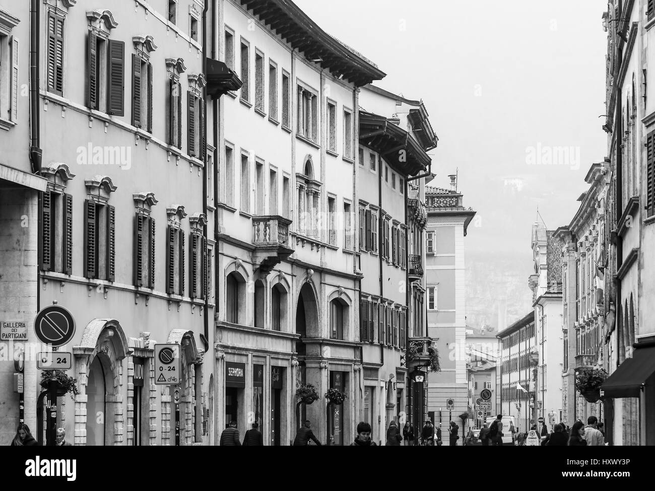 Trento, Italy - March 21, 2017: People in a shopping street in the old town with houses with diverse facades, cafes - Stock Image