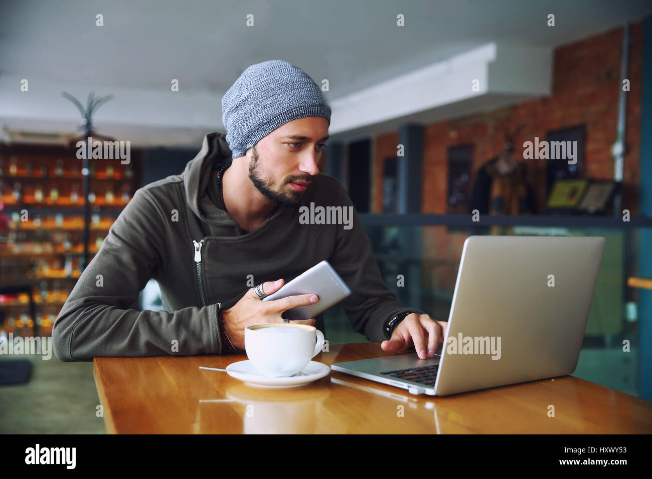 Young handsome hipster man with beard is using computer in cafeteria - Stock Image