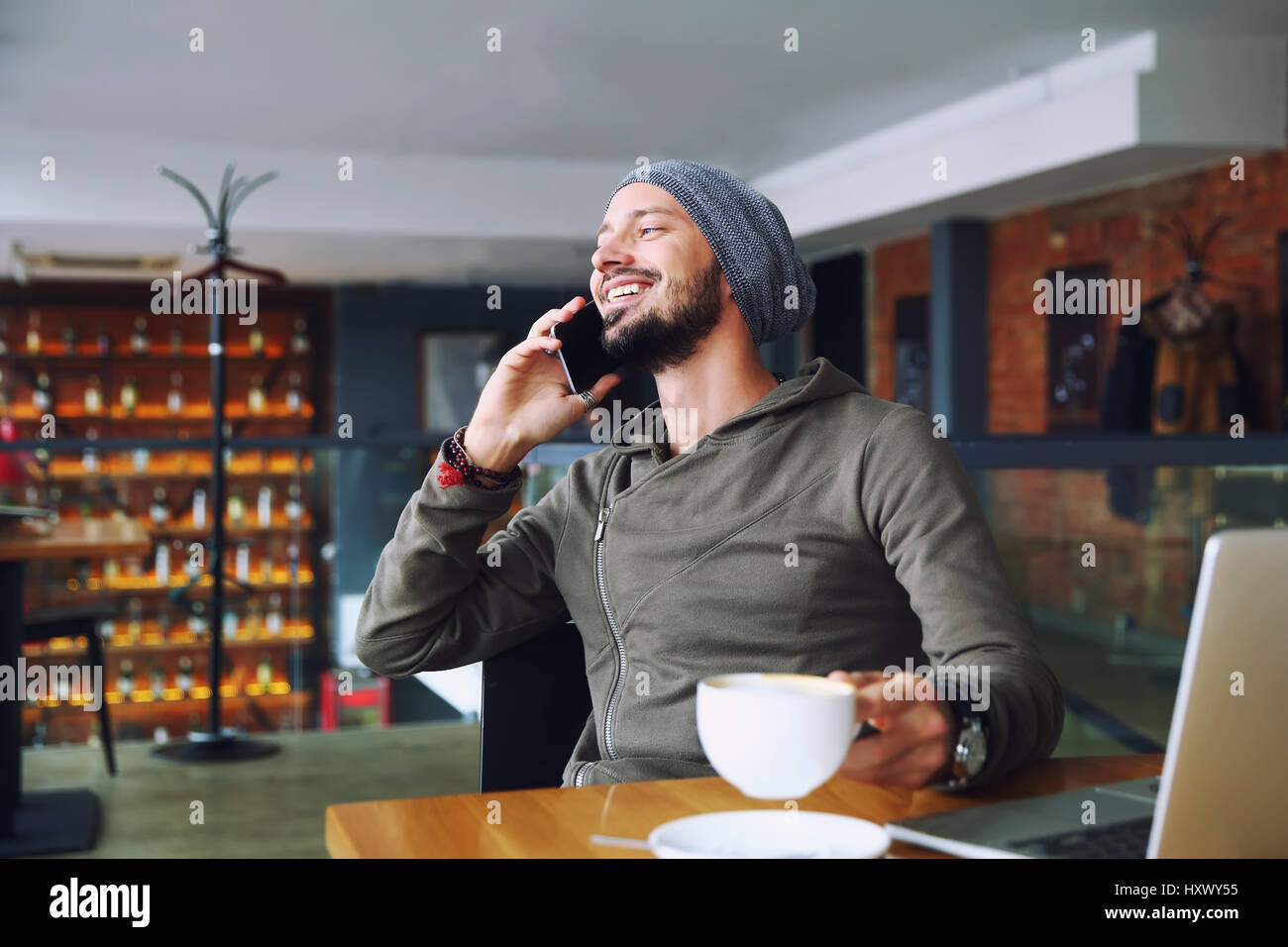 Young handsome hipster man with beard sitting in cafe talking mobile phone, holding cup of coffee and smiling. Laptop - Stock Image