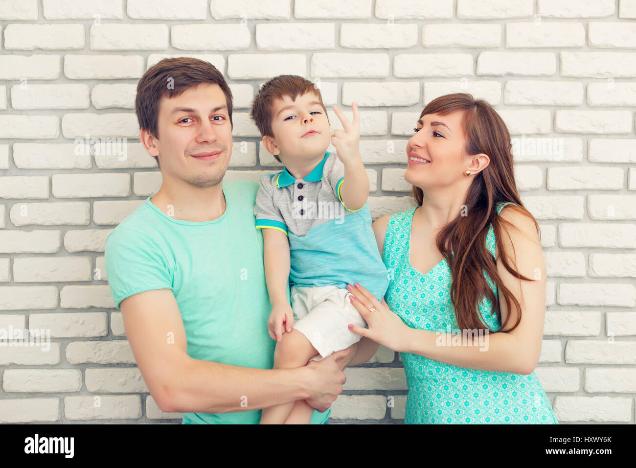 Happy and smiling young family Portrait on Brick wall Background. Father and Mother with Little Baby boy. Parents - Stock Image