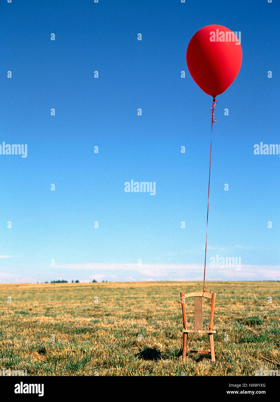 A red balloon tied to and empty child's chair. - Stock Image
