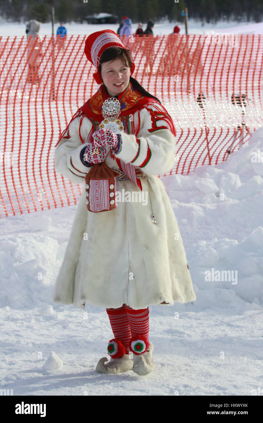 A dressed Sami woman observes while racers compete in reindeer race during St. Mary's Days festivities in Finnish Stock Photo