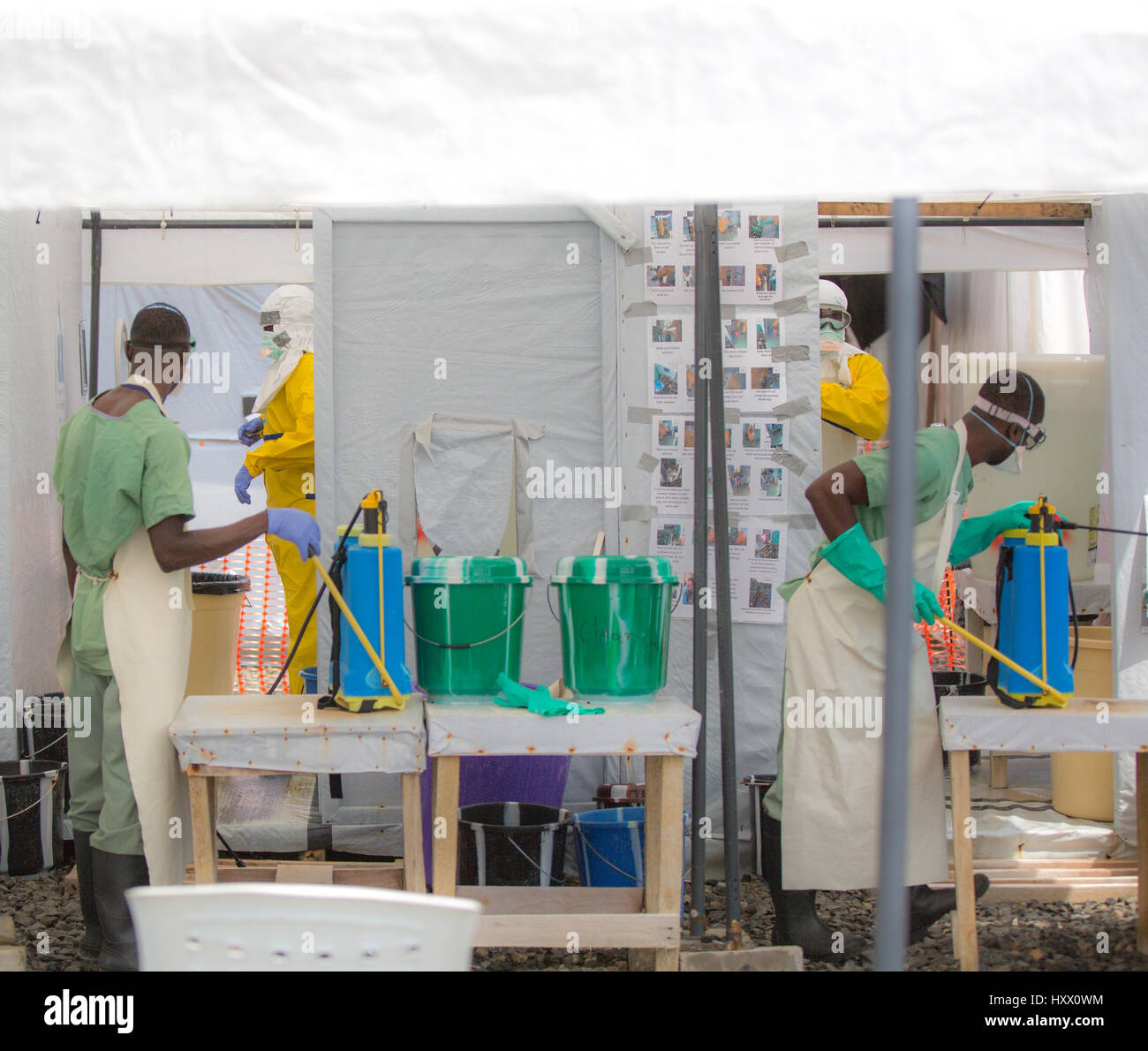 Sprayers at ELWA 1 disinfect healthcare workers entering and leaving this ETU in Monrovia set up by MSF. Everyone Stock Photo