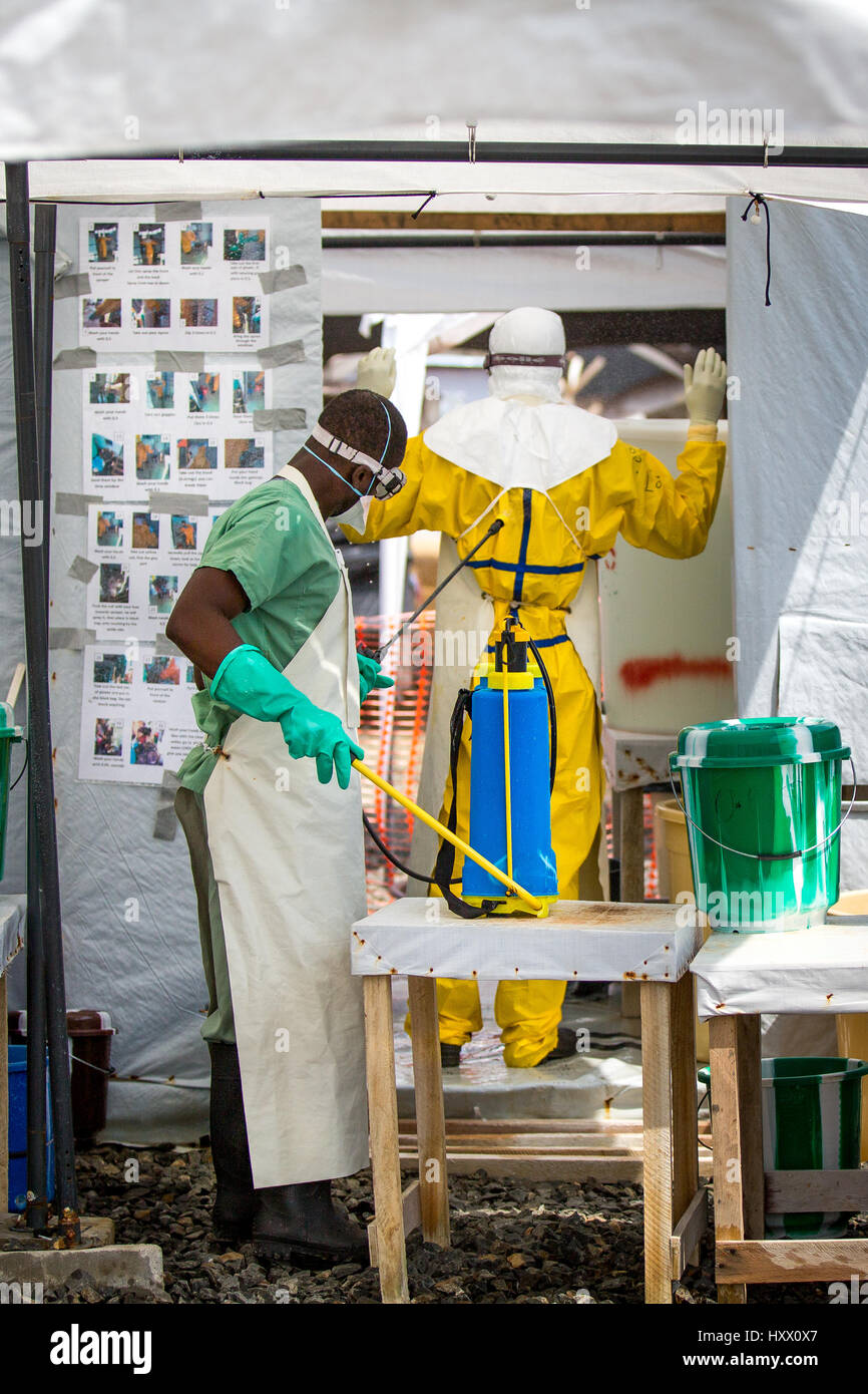Sprayers at ELWA 1 disinfect healthcare workers entering and leaving this ETU in Monrovia set up by MSF. Everyone - Stock Image
