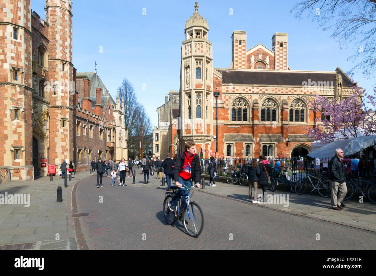 Cambridge university student cycling a bicycle past St Johns College Cambridge University, Cambridge England Cambridge - Stock Image