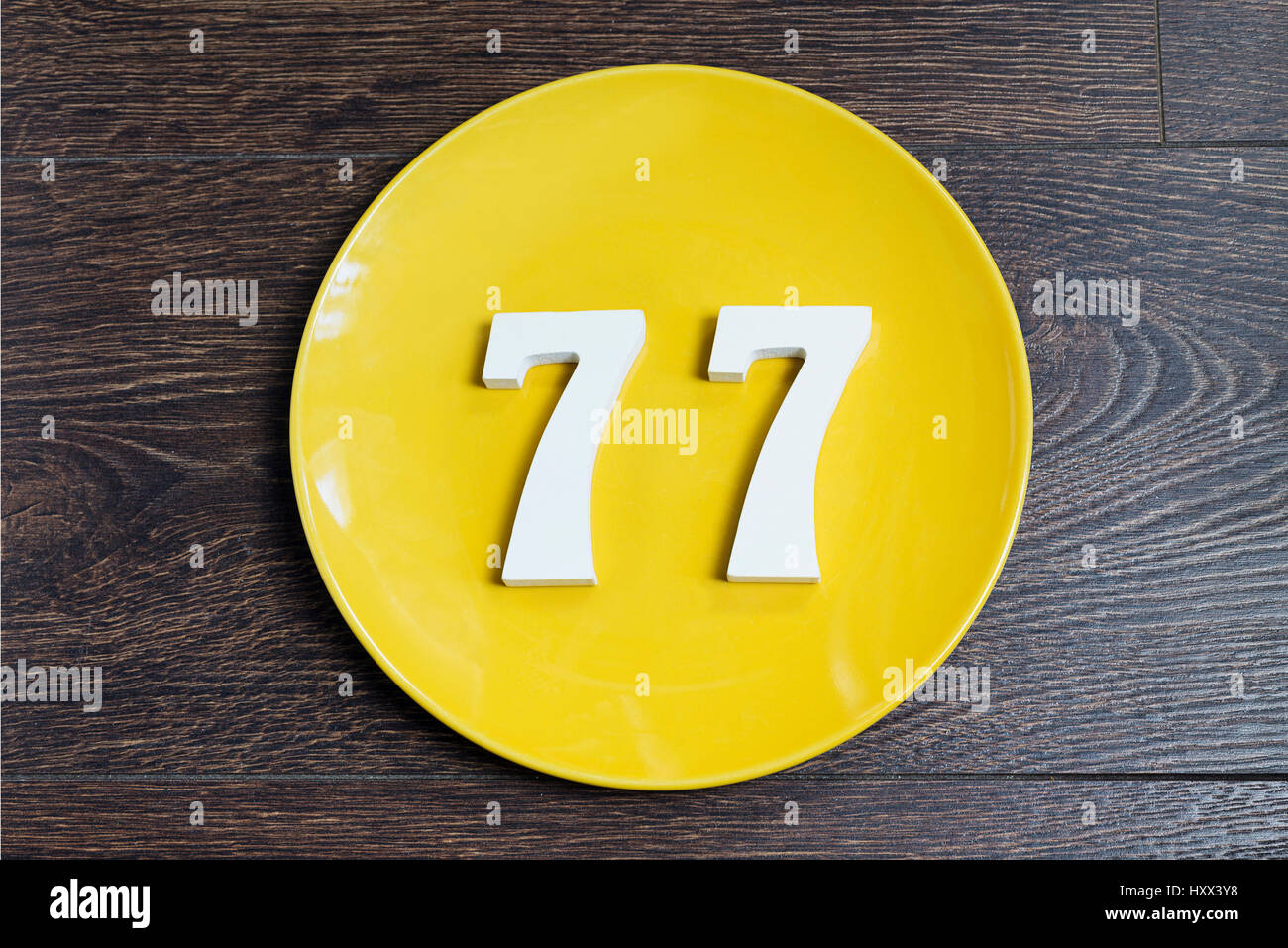 The number seventy-seven on the yellow plate and brown background. - Stock Image