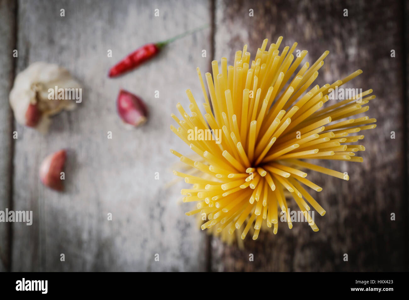Tied dried spaghetti pasta on a rustic background - Stock Image