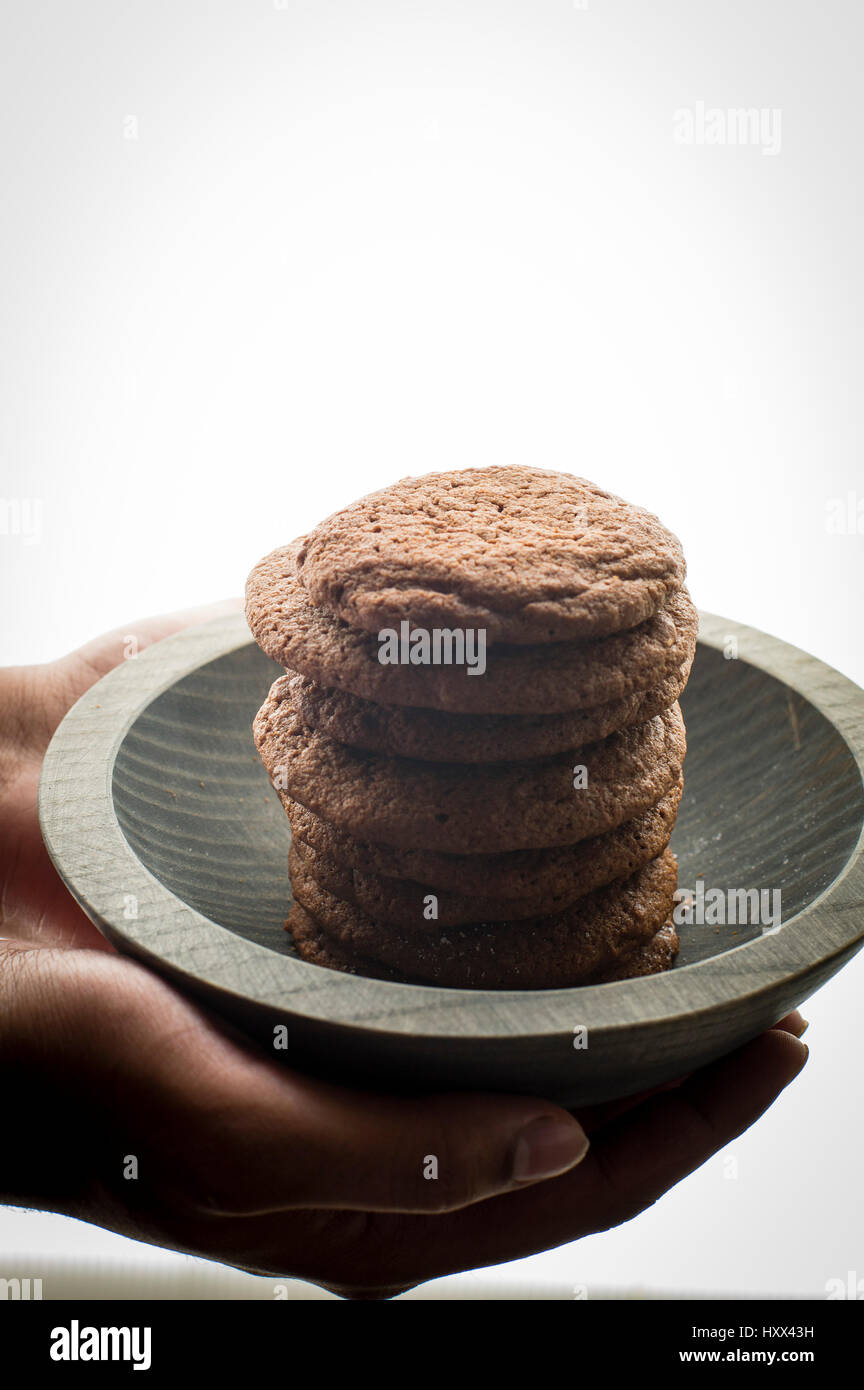 Stack of Brownie cookies in a grey wooden bowl model hands on shot backlit - Stock Image