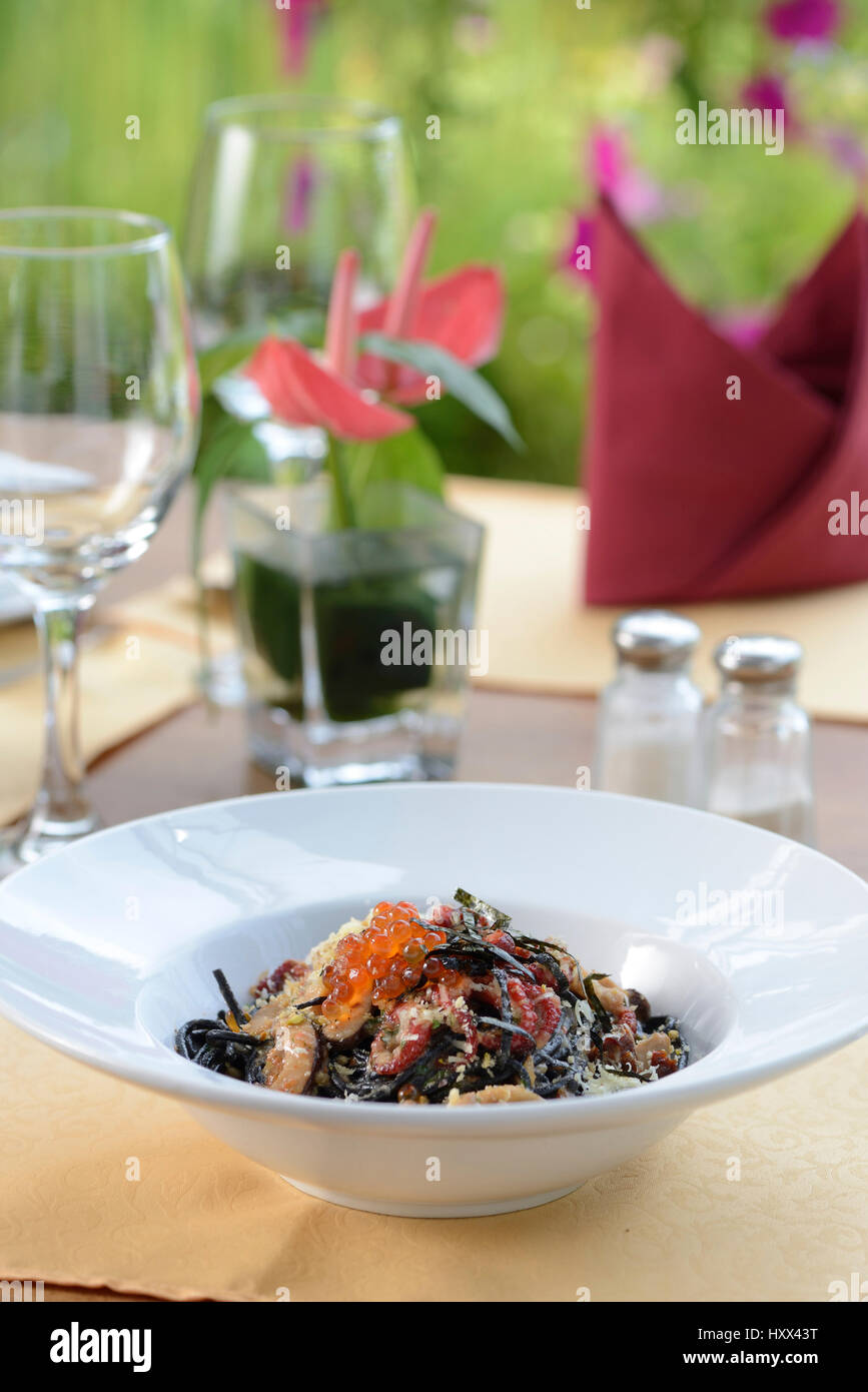 Seafood Ink spaghetti serve with table setup - Stock Image