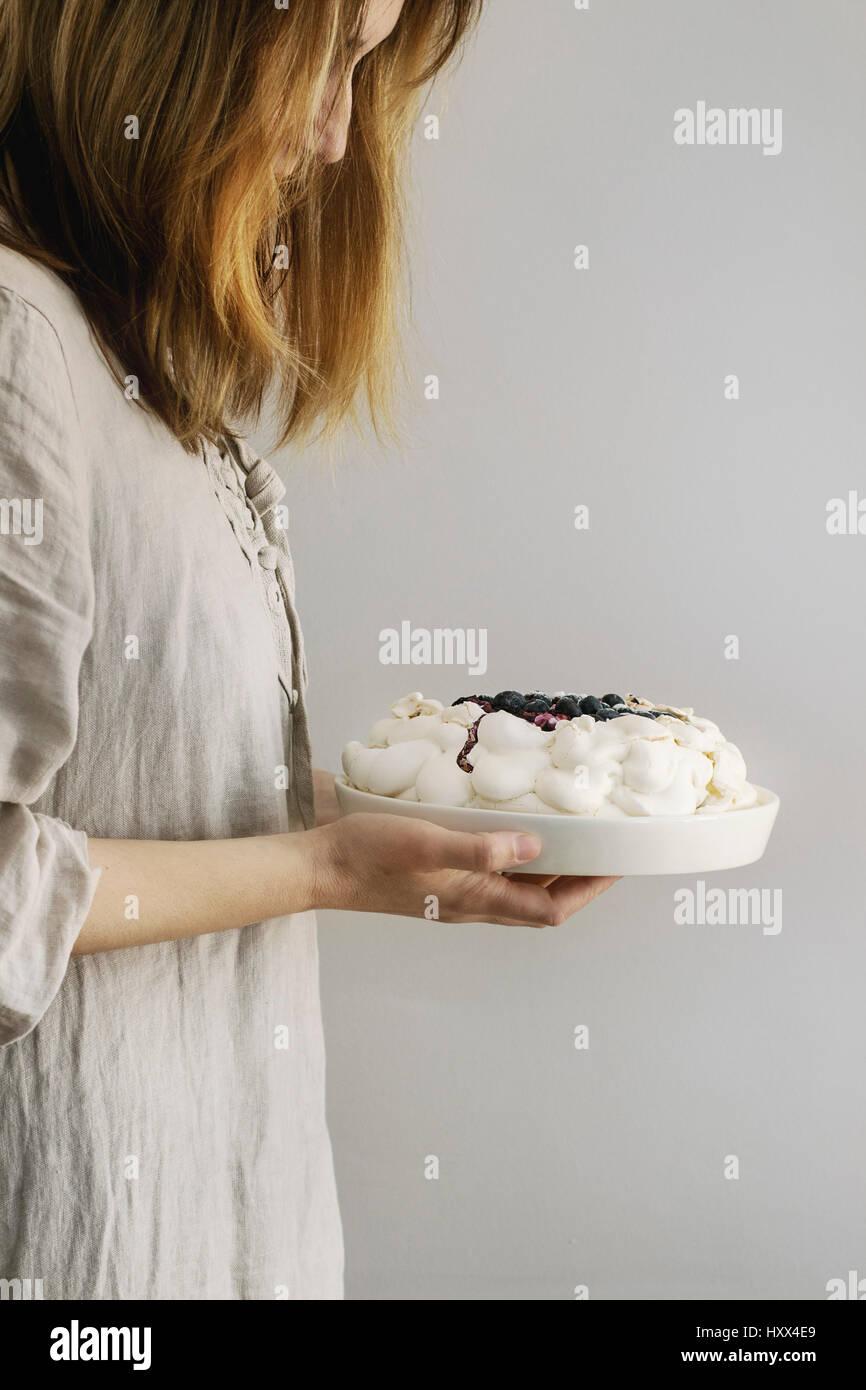 Woman tasting cake. Homemade meringue cake Pavlova with whipped cream, sugar powder, fresh blueberries and blueberry - Stock Image