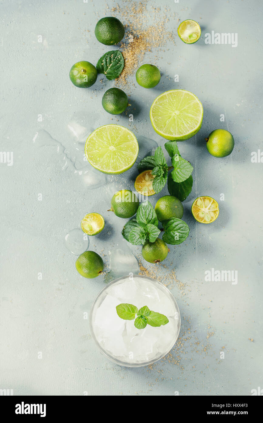 Ingredients for mojito cocktail, whole, sliced lime and mini limes, mint leaves, brown crystal sugar over gray stone - Stock Image