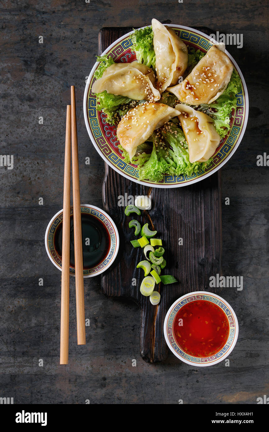 Gyozas potstickers on lettuce salad with sauces. Served in traditional china plate with chopsticks and spring onion - Stock Image