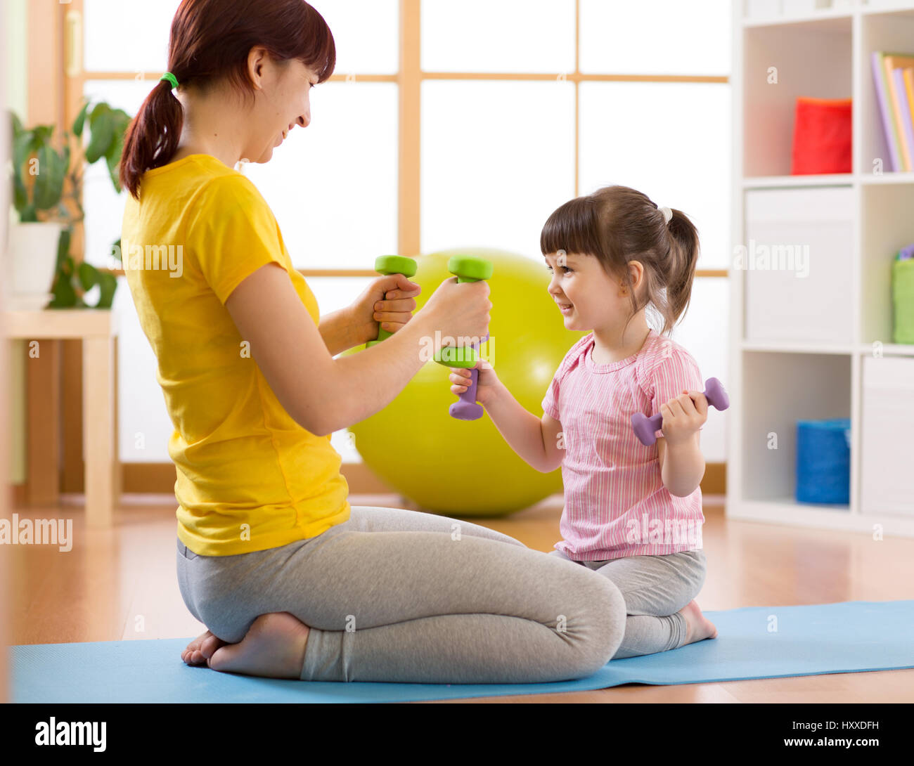 Mother and her child daughter doing fitness exercises with dumbbells - Stock Image