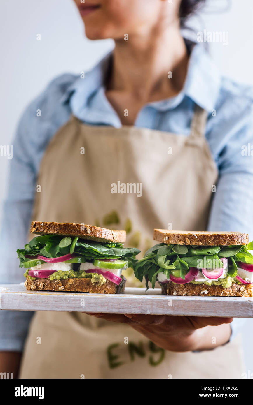 A woman with a blue shirt and a beige apron holding springtime feta sandwiches with herbs, avocado and pickled red - Stock Image