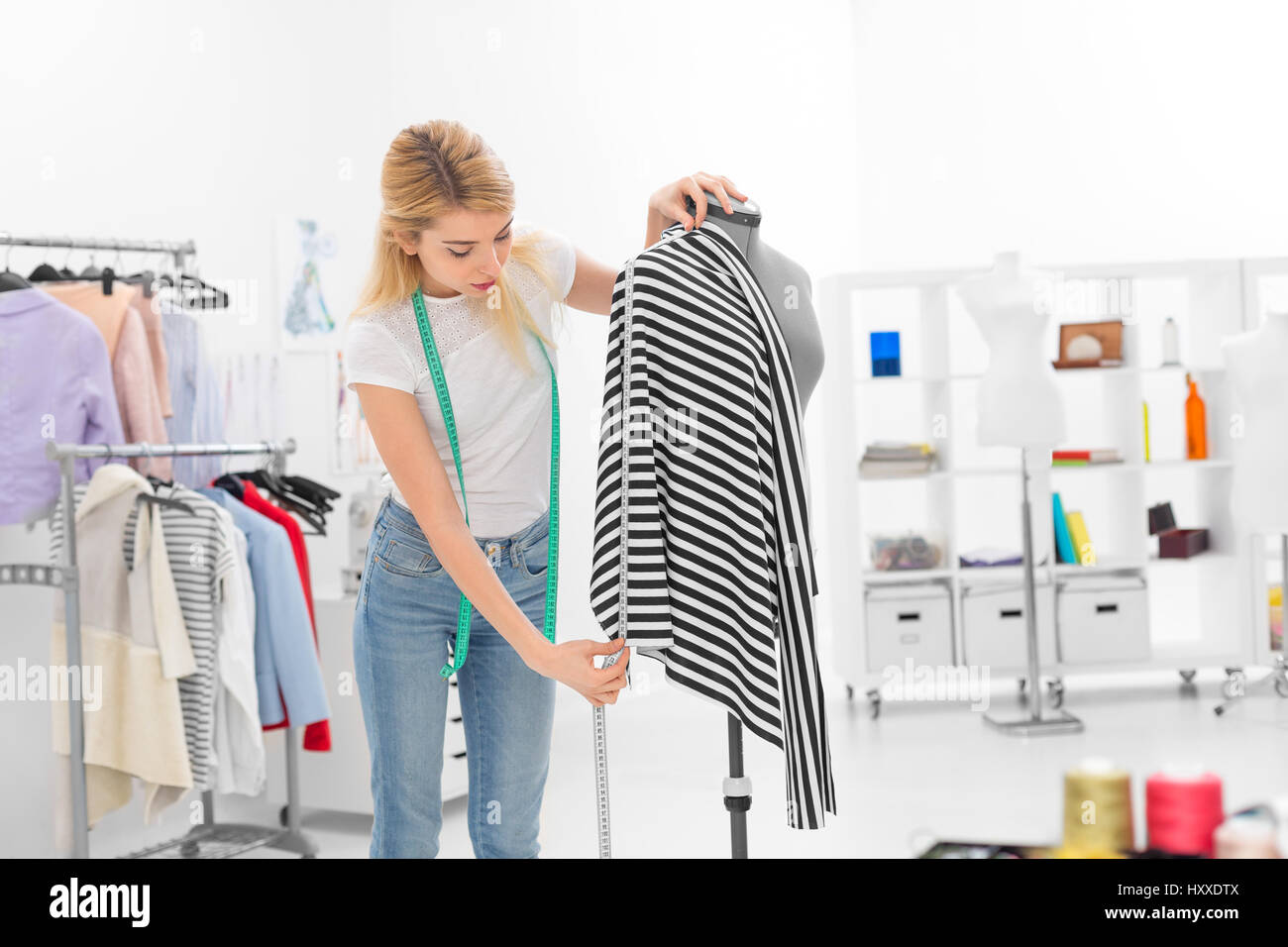 young fashion designer measuring fabric on mannequin - Stock Image