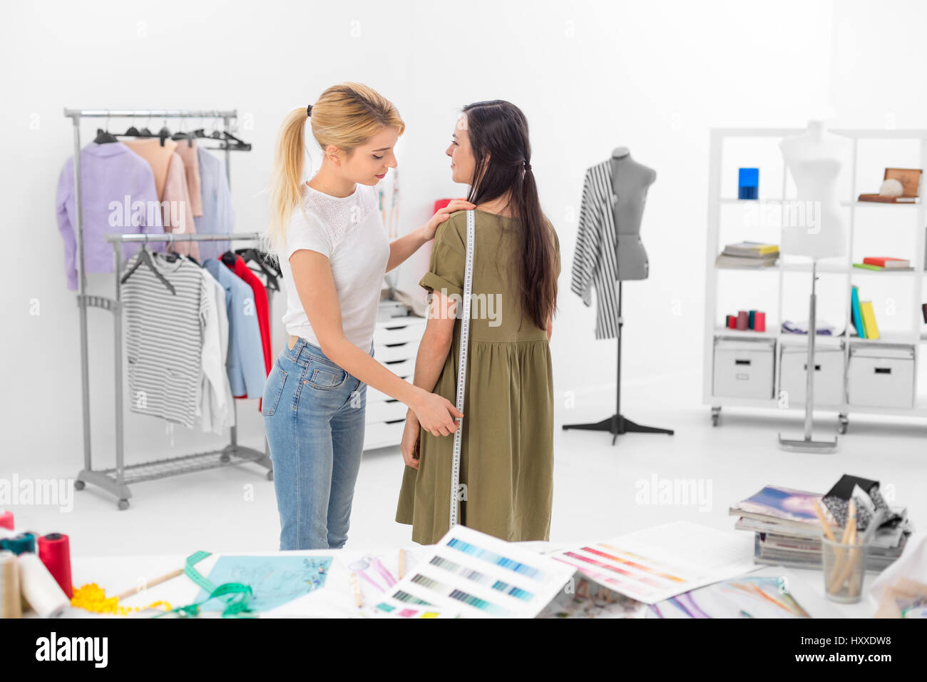young dressmaker gets hight measures of client in the showroom - Stock Image