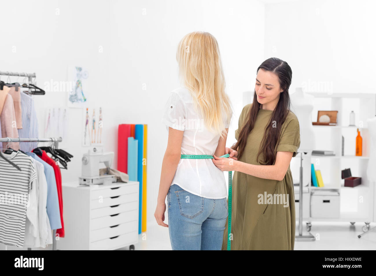 young dressmaker gets waist measures of client in the showroom - Stock Image