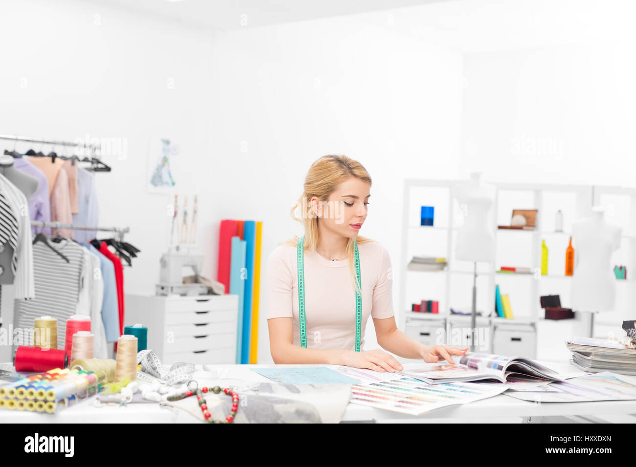 young fashion designer sitting at the desk in her workshop looking throught magazines - Stock Image