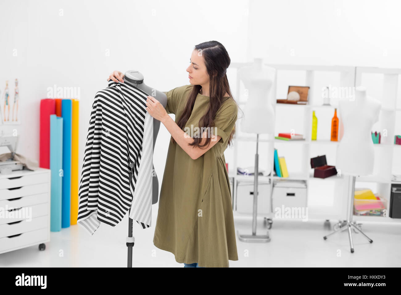 young fashion designer adjusting fabric on mannequin - Stock Image