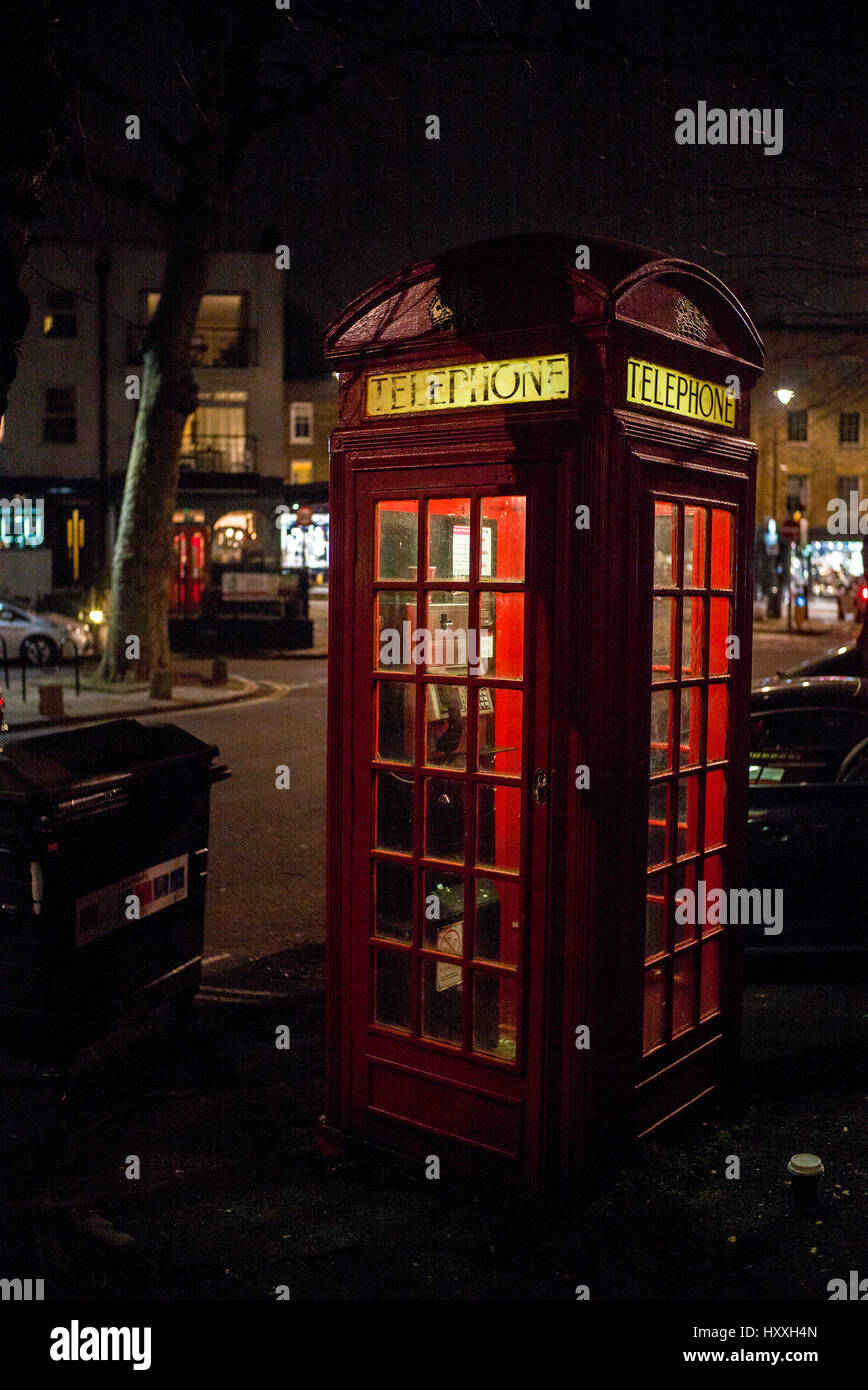 British red telephone box illuminated from within at night - Stock Image