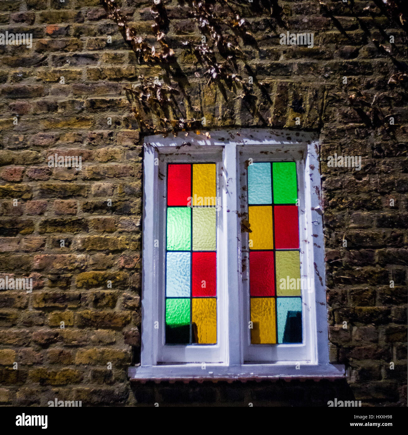 stained glass window illuminated white painted window frame in brick wall - Stock Image