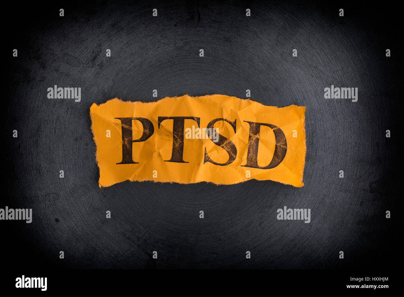 Torn pieces of paper with abbreviation PTSD. Posttraumatic stress disorder. Concept Image. Closeup. - Stock Image