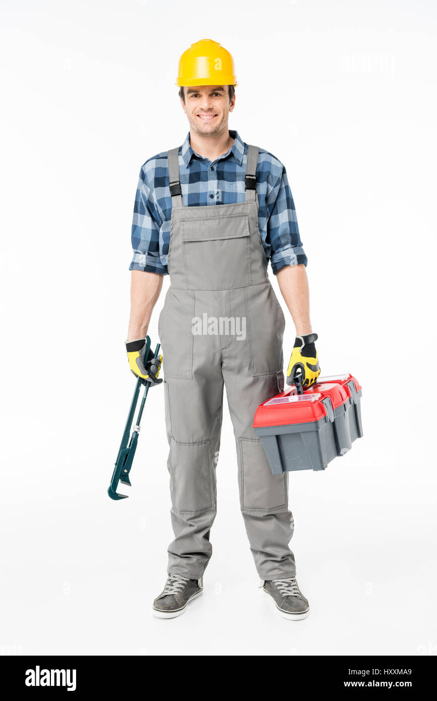 Smiling workman in hard hat holding tool kit and looking at camera on white - Stock Image