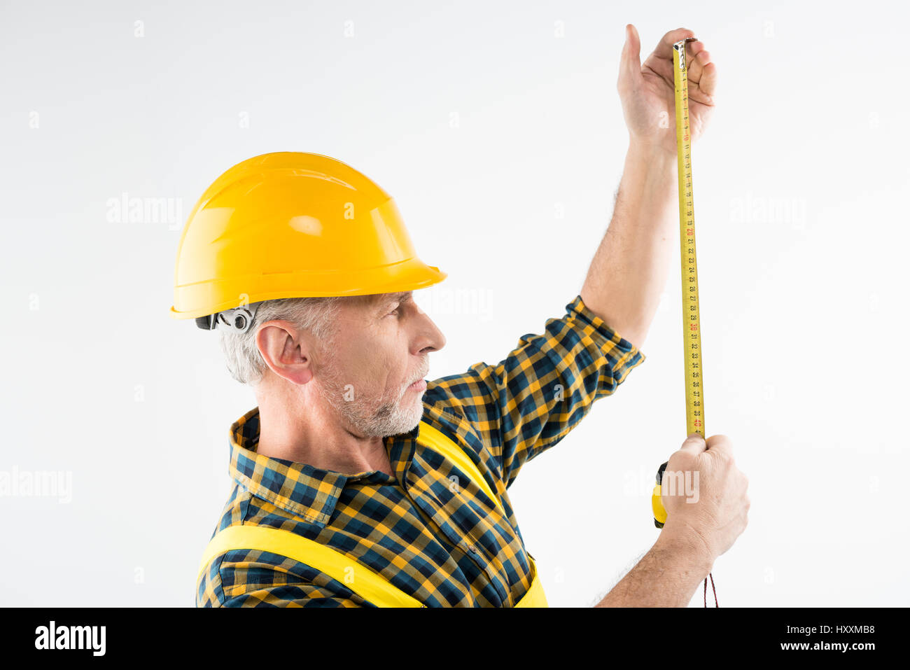 Mature workman in hard hat  working with flexible ruler - Stock Image