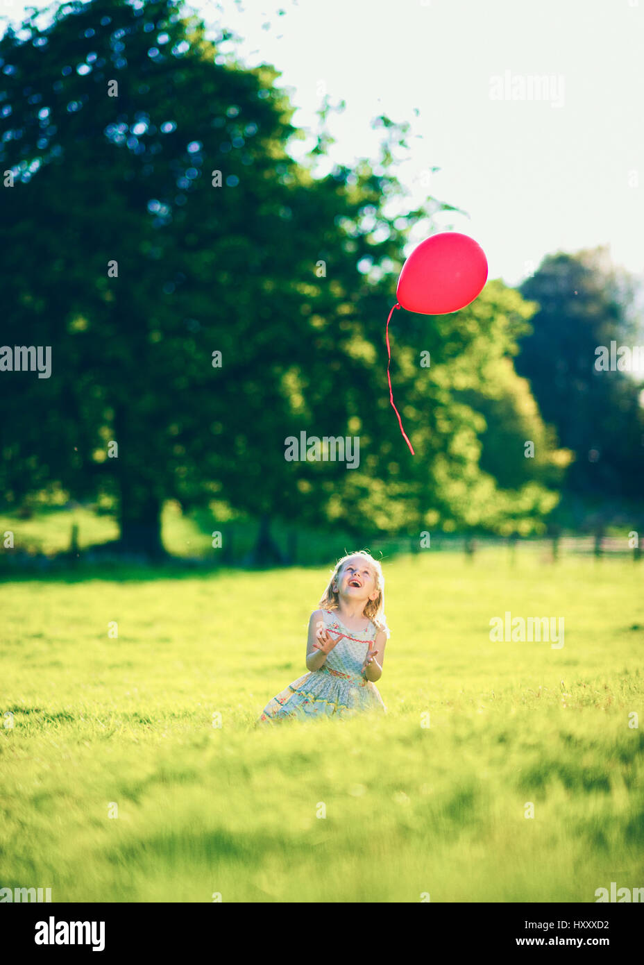 Blond girl letting go of a single red balloon in the Countryside - Stock Image