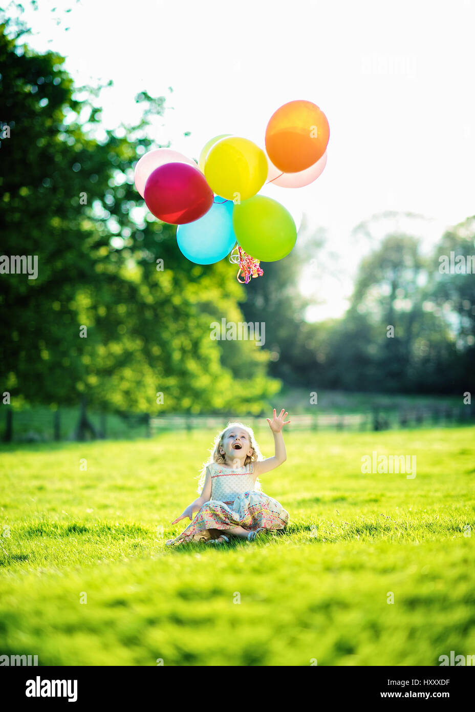 Blond Girl Playing with bunch of balloons in the countryside - Stock Image