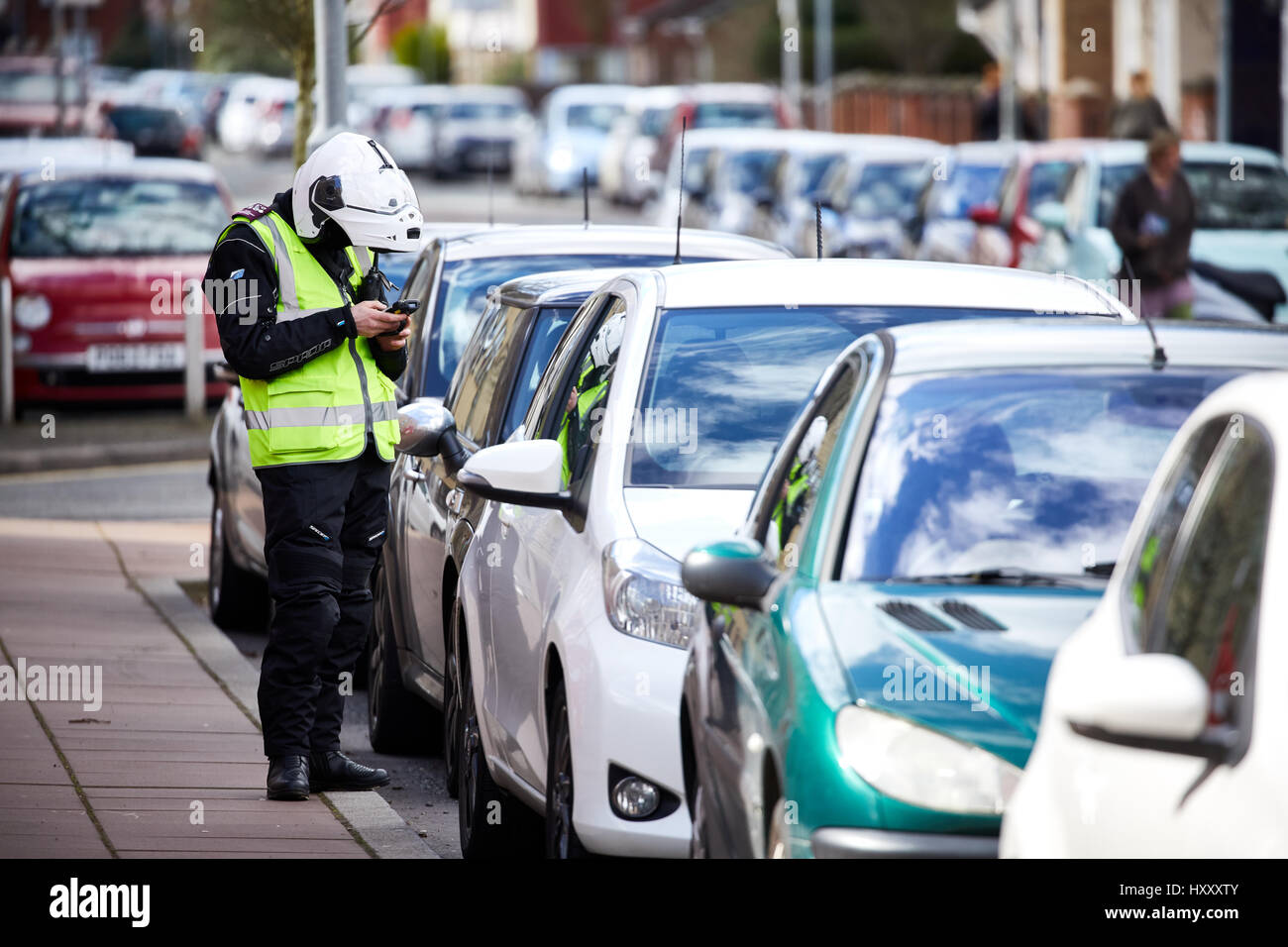Parking enforcement offices in motorbike gear checking street parking in Hulme, Manchester, England, UK. - Stock Image